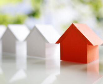 several white mini plain wood houses with one red house Tanner Berkey, MBA, REALTOR