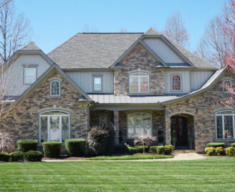 large stone home with manicured grass front yard in Colorado Tanner Berkey, MBA, REALTOR