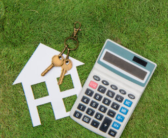 cut out of house, two keys and calculator in the grass, buying a house Tanner Berkey, MBA, REALTOR